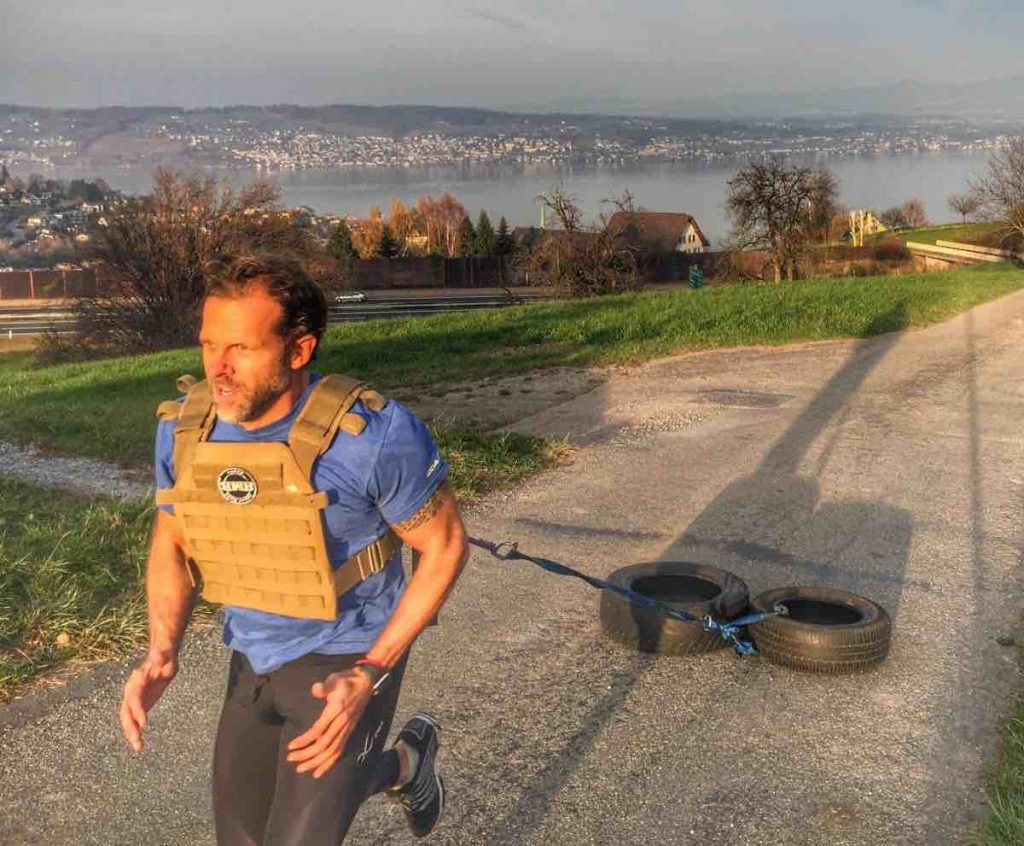 Picture of a man running uphill wearing a weighted vest