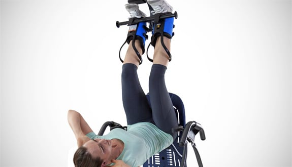 Picture of a woman using gravity boots and curling up