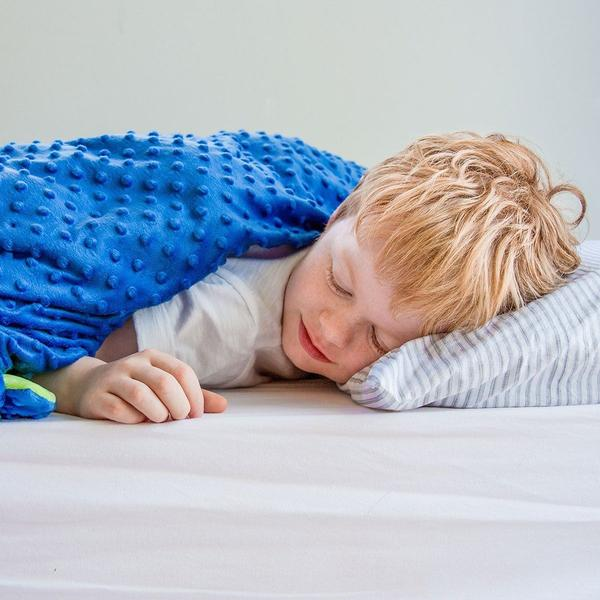 Picture of an autistic child using a sensory blanket