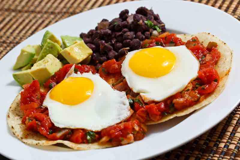 Picture of a healthy plate of huevos rancheros with eggs, beans, and more essential energy boosters