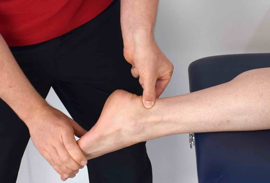 Picture of a physical trainer stretching a man's ankle joint